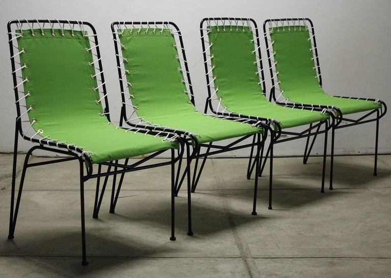 Beautiful set of four restored Pipsan Saarinen-Swanson outdoor patio sitting chairs for Ficks Reed, circa 1949. The have wrought iron frames with canvas seats. The canvas has been redone and the frames are freshly painted. All the rope and grommets