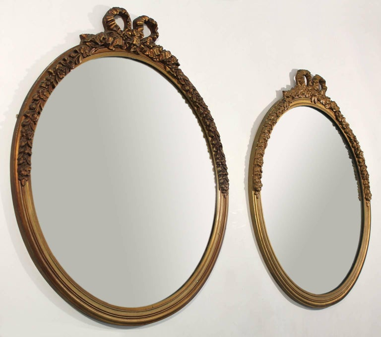 Great original antique pair of gold gilt painted carved wood mirrors. Beautiful ribbon/bow decorations done in plaster over wood. Has the original mirrors. In the style of French Baroque. These are 100% original and in very nice original condition.