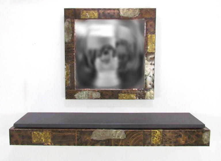 Wall-mounted patchwork metal clad console shelf with slate top by Paul Evans for Directional with matching mirror, circa 1970s.    Shelf measures 60