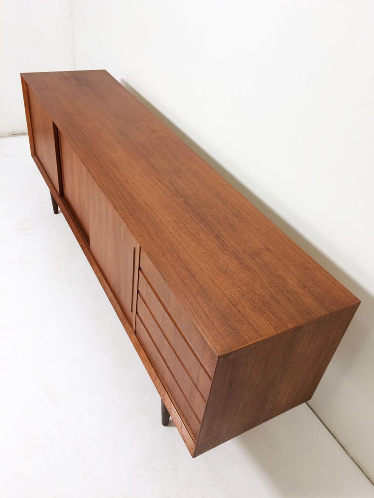 Classic teak credenza by Alderslyst Mobelfabrik, made in Denmark, circa 1960s. Book matched door and drawer fronts. Shallow drawers to the right including one felt lined for silverware storage; shelving storage behind the sliding doors to the left.