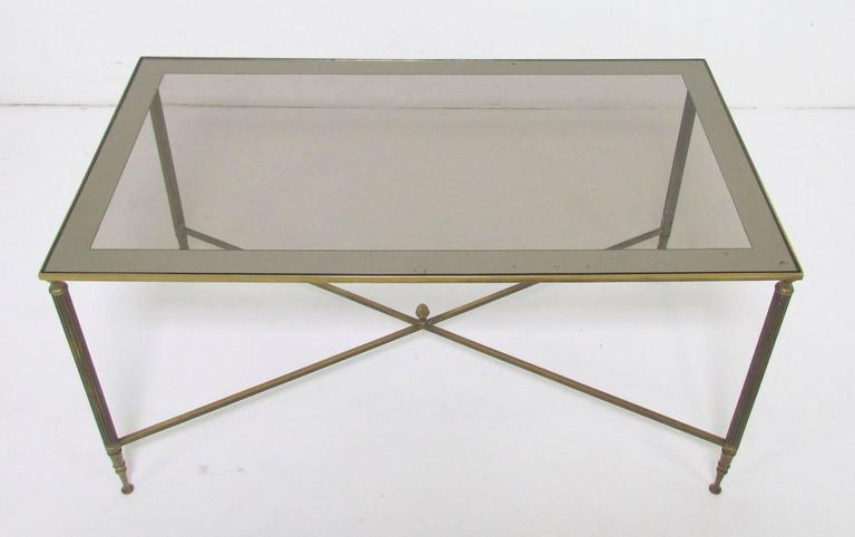 Coffee or cocktail table in solid brass in the style of Maison Jansen, circa 1960s. Cross form stretcher with acorn finial, reeded columnar legs. Inset smoked glass top with mirrored border.