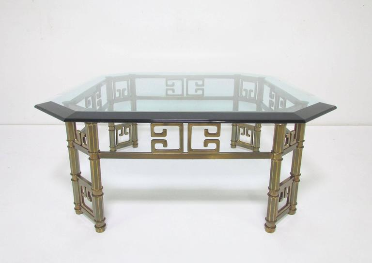 Substantial Mastercraft coffee table in brass with a decorative Greek key motif, canted legs support a thick beveled octagonal glass top.