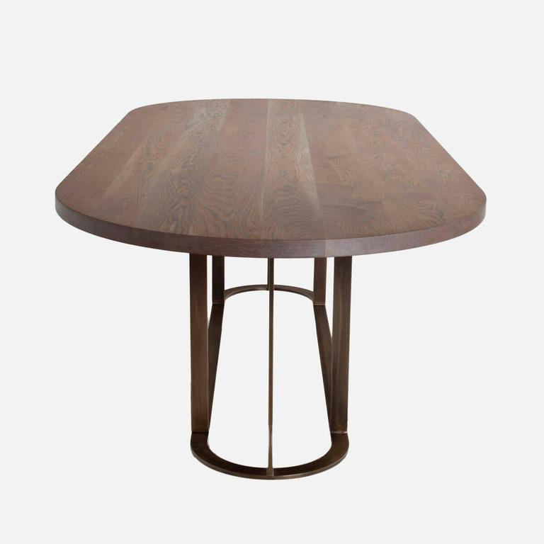 A custom dining table consisting of a structural metal base and a solid figural wood top in a variety of finishes. See finish options in last image. The Colyer table is available for custom order with a lead time of 8-10 weeks. Sometimes we're able