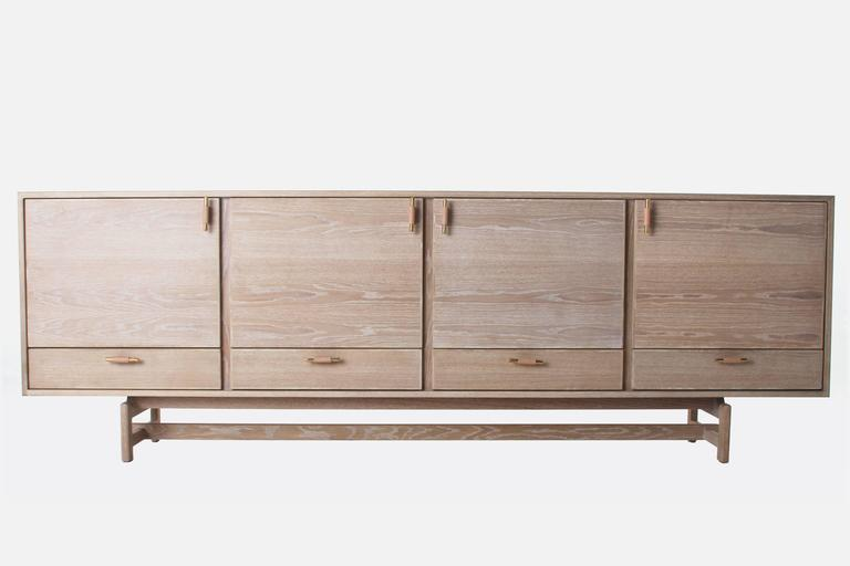 A custom credenza consisting of a solid wood base and vegetable dye leather wrapped solid polished brass pulls. Various combinations of the slatted media cabinet doors, regular doors, and drawers are available. Please inquire for more information on
