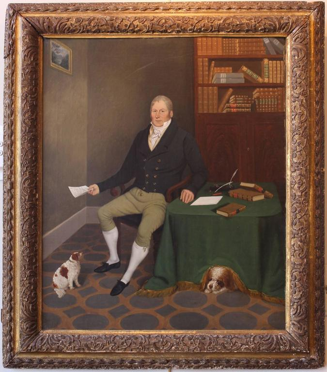 A beautifully painted and very charming English oil painting of a seated gentleman in a library setting with his two adoring King Charles Spaniels. Signed on the back right corner of the lined canvas by listed UK artist Edmund Ward Gill, 1794-1854.