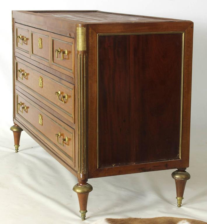 A 19th Century French Louis XVI style mahogany commode, the original gray marble top above three long brass-mounted drawers with rectangular handles. The column form ends mounted with brass washboards and fluting, raised on turned tapering feet with