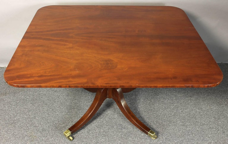 An early 19th Century English mahogany tilt-top breakfast table with rectangular top and turned column on a quadripartite  base.