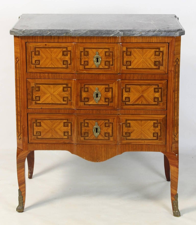 A small and elegant mid 19th C. Louis XVI style satinwood and tulipwood parquetry three drawer commode with gilt bronze fittings and original gray marble top.