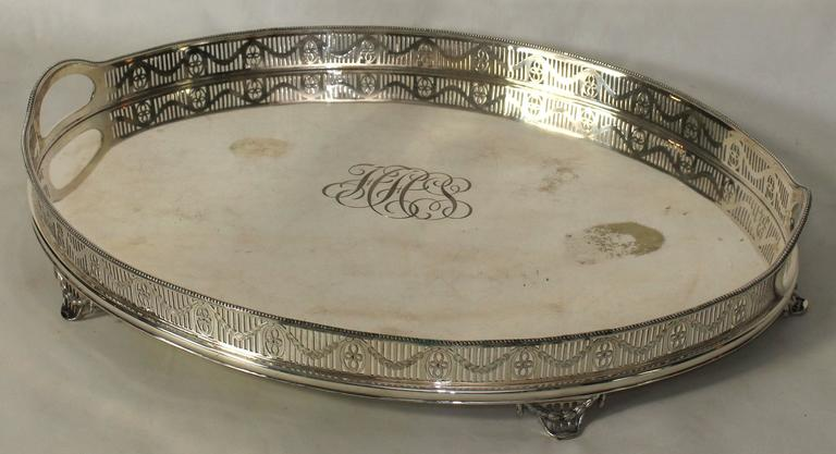 A large oval English Sheffield silver gallery tray with elaborate monogram engraved in the center.