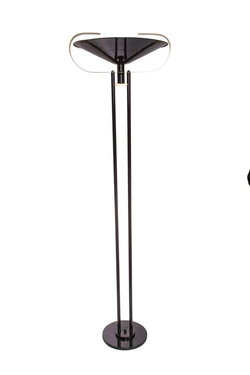 A modernistic torchiere floor lamp, produced circa 1950s in black enameled metal with dual stem, the inverted shade accented with curved brass bands. Very good vintage condition, wear consistent with age and use.