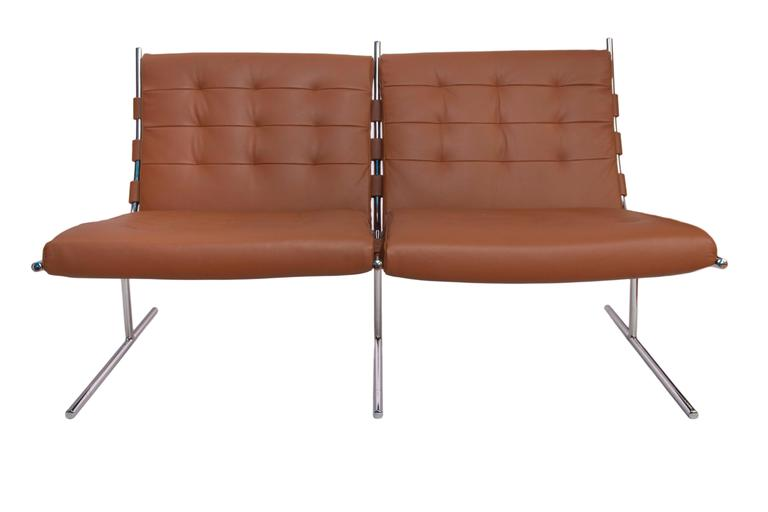 A Brazilian modern two-seat sofa by designer Jorge Zalszupin, manufactured circa 1960s, with tufted backs and seats in caramel colored leather, against chrome frame and 'T Invertido' base. Excellent vintage condition, recently reupholstered.