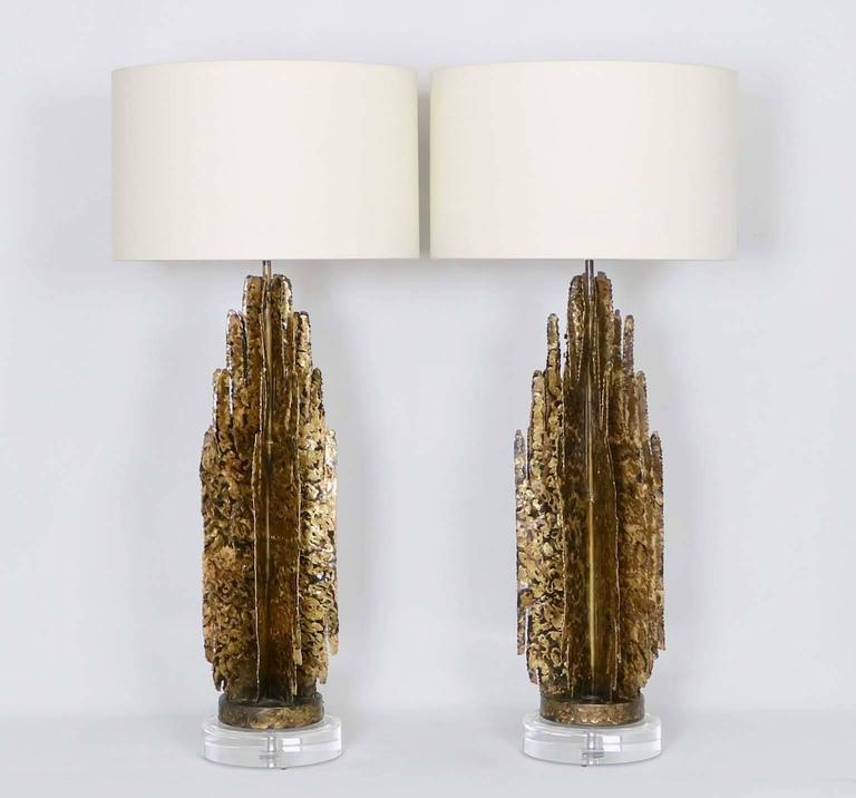 A pair of monumental Mid-Century Modern Brutalist abstract sculptural table lamps in the manner of Paul Evans, crafted of gilded tole with Lucite bases. The noted height is to the finial, the height to the top of the sculpture body is 29 in.