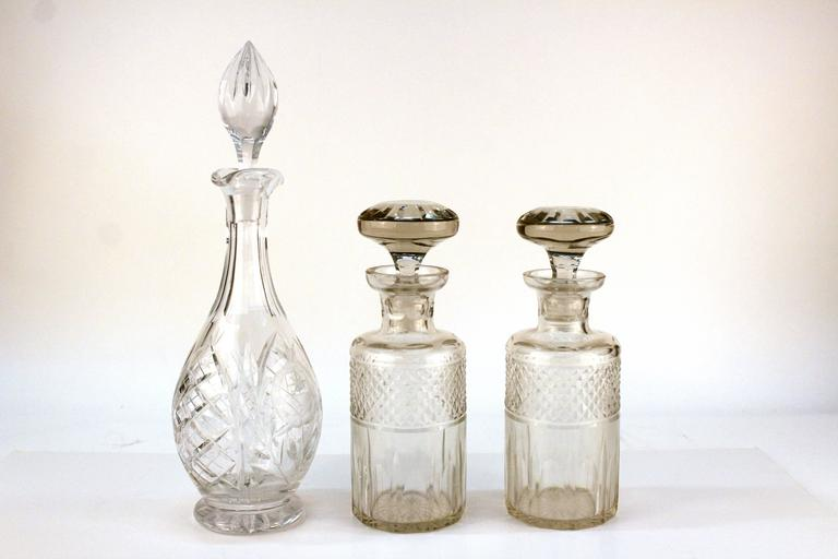 Set of three decanters. Includes a pair in a darker clear crystal, and a large bonus decanter with etched details and a flame stopper.   Measures: Pair: 10 in. H x 3.5 in. D Large: 16 in H x 4 in. D.  110596.