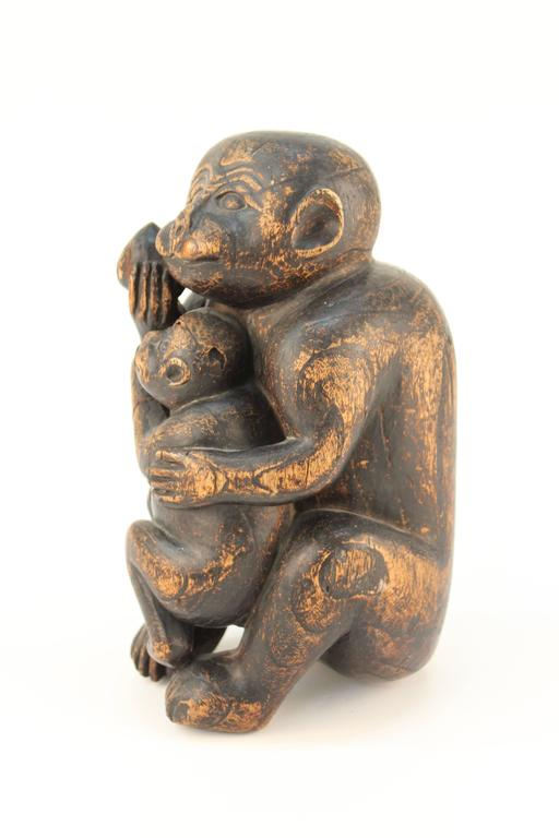 A sculpture of a monkey holding a peach in one hand and her baby in another. Carved out of wood. Despite some signs of wear to the wood, the sculpture remains in good vintage condition. 110598.