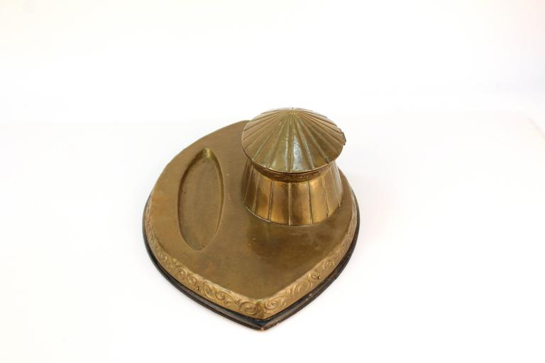 A vintage brass inkwell of the Arts & Crafts Movement. A circus tent shaped pot sits on an almond shaped base with a small indent for pens, intricate swirls decorate the sides. In good vintage condition.  110607