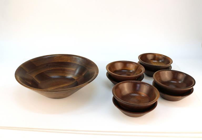 """A set of Vermilion walnut bowls. Includes one large salad bowl and eight serving plates. Despite some minor wear, the set remains in over all good condition.   Measures: Large bowl dimensions: 3"""" H x 12"""" D. Serving bowls: 3"""" H x 6"""