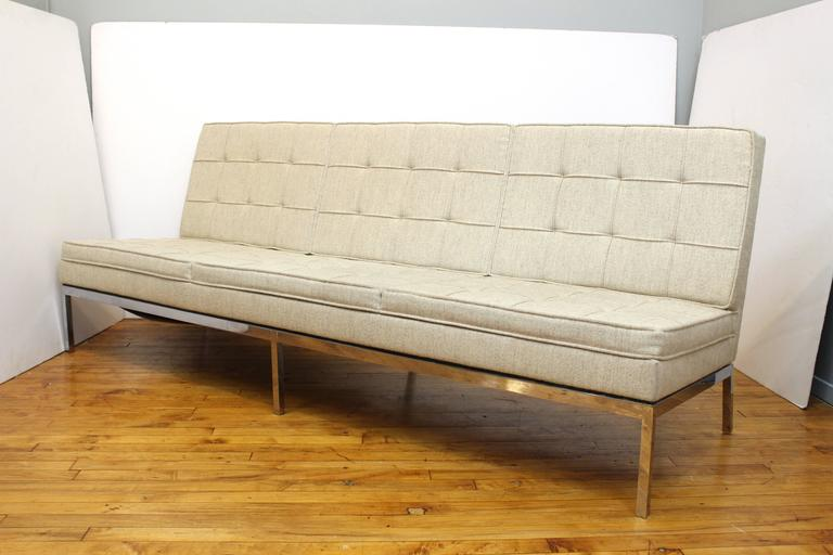 A three-seat sofa by Florence Knoll for Knoll. Classic Mid-Century design in chrome, with tufted and box stitched cream fabric. Includes original Knoll label on base.   110714.