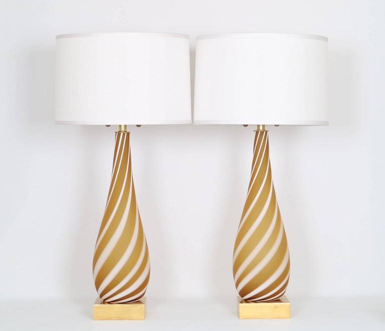 Pair of Mid-Century Modern Murano glass lamps in butterscotch with a white ribbon swirl and mounted on a gilded wooden base. The noted height is to the finial,the height to the top of the glass body is 23.5 in (60 cm). Fully restored with all new