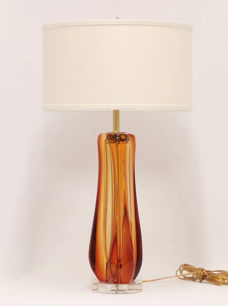 Mid-Century Modern lamp by Galliano Ferro in deep amber Murano glass, mounted on Lucite base.The noted height is to the finial. The height to the top of the glass body is 17.5 in ( 44.5 cm).Fully restored with all new wiring and hardware.Please note