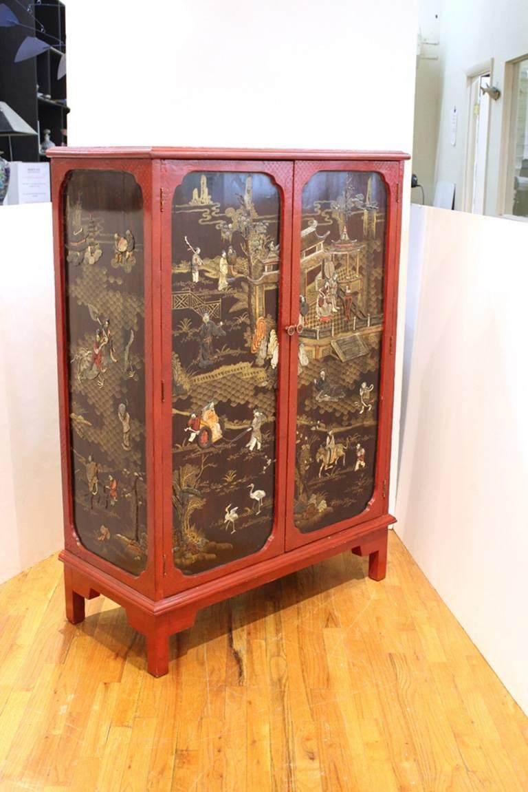 This chinoiserie cabinet in red and black features fantastical illustrated scenes of godly life on both the exterior and interior of the cabinet.