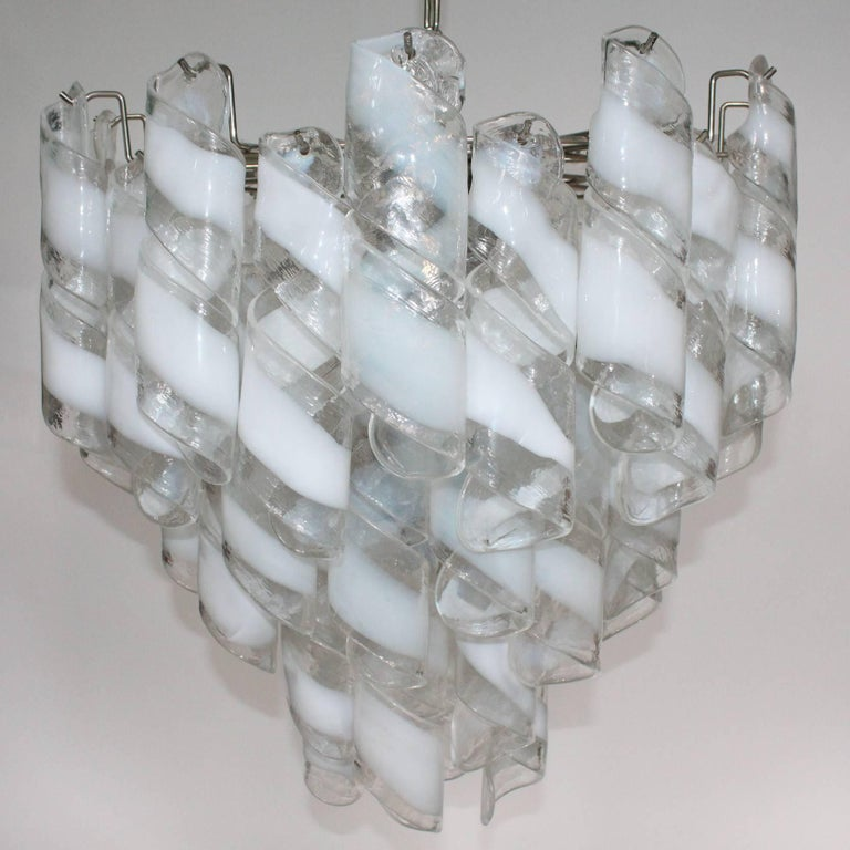 A Murano glass chandelier by Mazzega. Includes tiers of clear and white Murano Glass spiralled ribbons. In good condition.