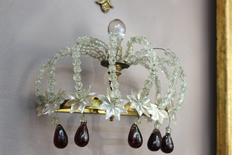 A pair of sconces in the shape of crowns. Crafted in clear rock crystal beads on brass base with stars on the band and dangling plum colored drops. Purely decorative, the pieces do not hold candles or include lights. Despite a missing drop on one