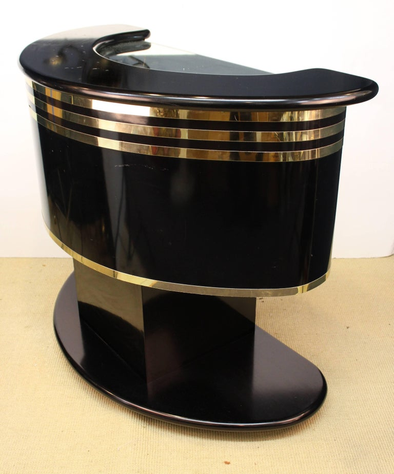 Hollywood Regency style half moon bar after Guzzini. Crafted in black laminate with mirrored glass accents and wood. Some bubbling of the laminate on the bar top and a small nick to the finish on the back. The bar remains in good vintage condition.