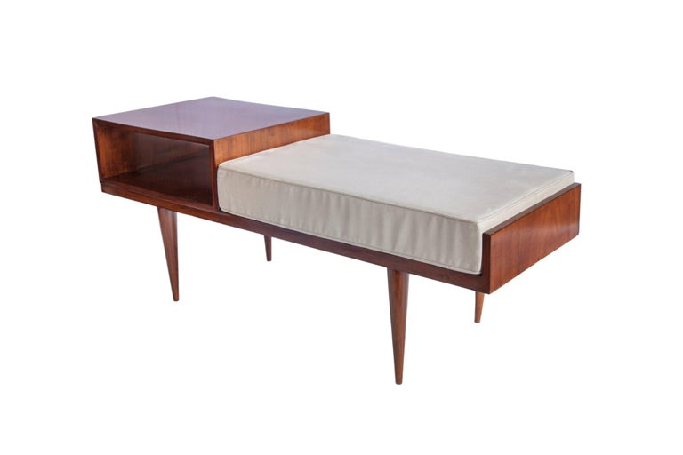 Mid-Century Modern telephone seat in Brazilian jacaranda wood with upholstered seat and built-in side table on tapered legs. The built-in side table features a hollow storage shelf. The seat has been recently reupholstered in beige artificial suede.