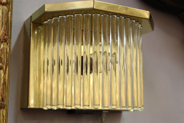 A pair of Mid-Century Modern brass and glass sconces made by designer Gaetano Sciolari in Italy in the 1970s. The brass frame holds a semi-circular row of glass rods that surround the light source. In great vintage condition with age appropriate