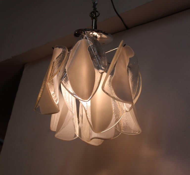 A Mid-Century Modern chandelier with folded glass leaves made of white and transparent glass. The piece has recently been rewired for US standards and is in great vintage condition.