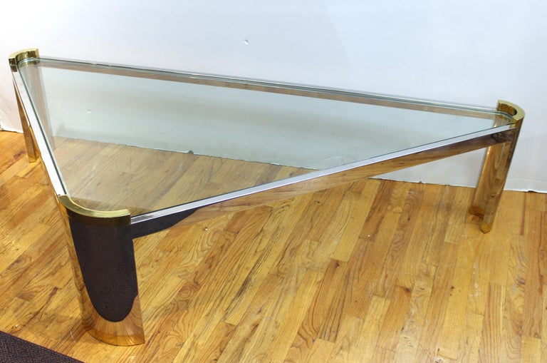 Jay Spectre coffee or cocktail table in the Modernist style. The table features a triangular shape, and clear glass top held by a silver-tone metal frame. The piece stands on three curved legs with gold-tone accents. Minor wear appropriate to age
