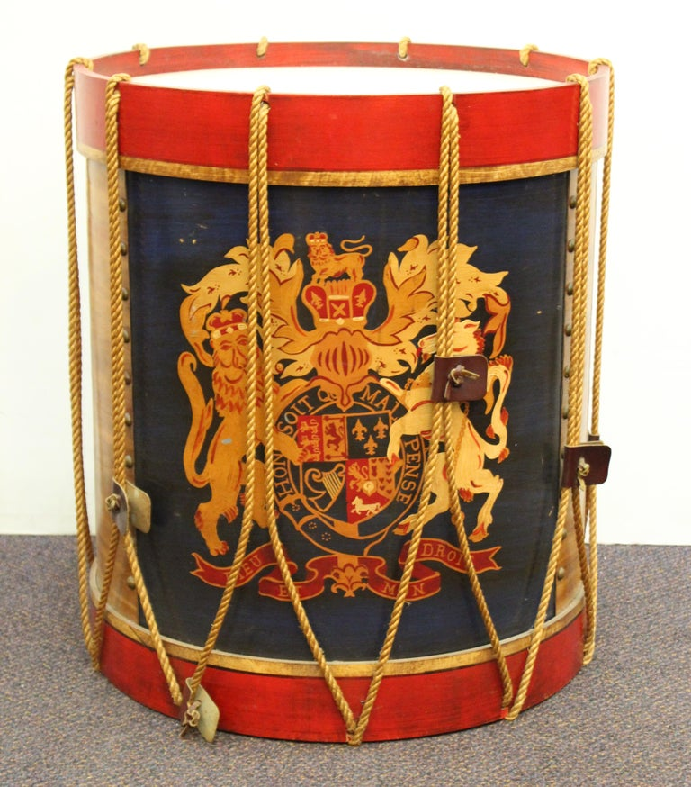 Hollywood Regency style pair of side or end tables in the shape of regimental British drums. The pair has cord and leather detailing and hand-painted British coat of arms. Some of the leather detailing is missing and a few of them are missing. In