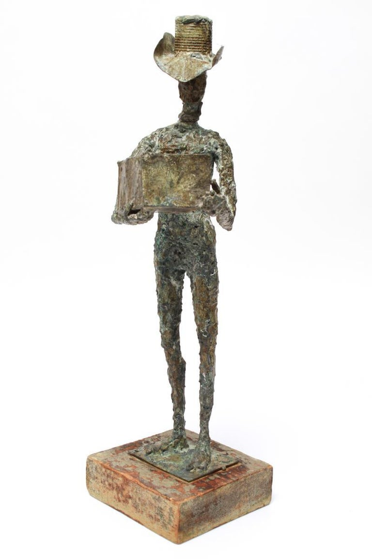 Mid-Century Modern Brutalist green-patinated bronze sculpture of a cowboy holding up a box, mounted on a wood base. The head appears to have been cast separately and attached. Some wear to the paint on the base.