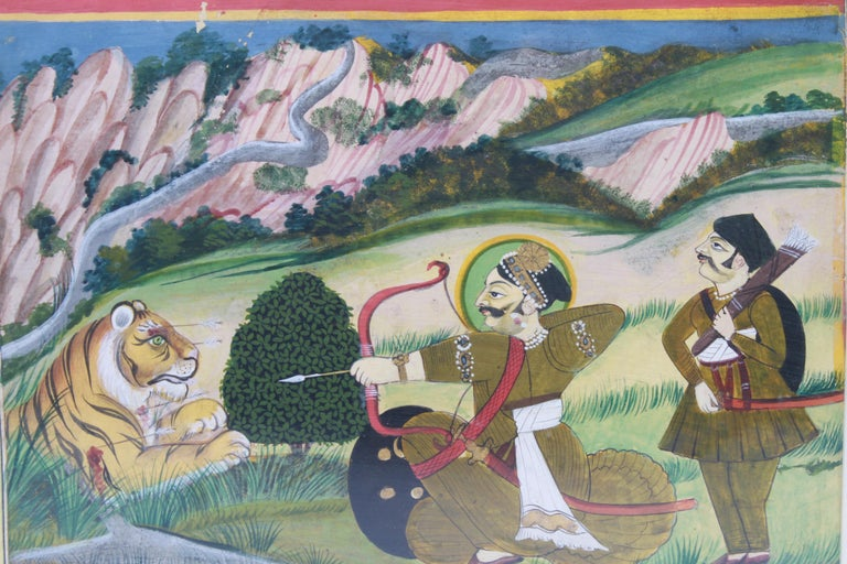 Eastern Indian framed gouache on paper painting depicting an archer and his servant, with bow and arrow, aiming at a wounded tiger with a landscape. The piece is framed and in good vintage condition.