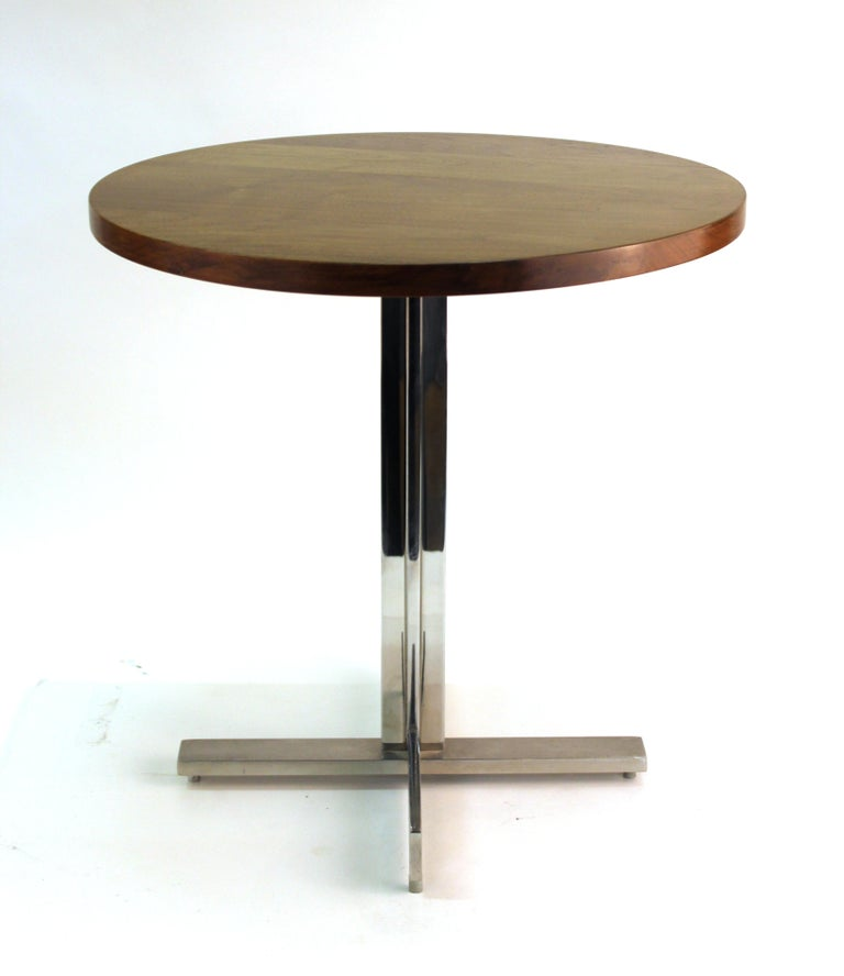 Mid-Century Modern round side table with walnut top and stainless steel base, designed in the style of Hans Eichenberger, designed in the 1960s. In great vintage condition with age-appropriate wear to the metal surfaces.