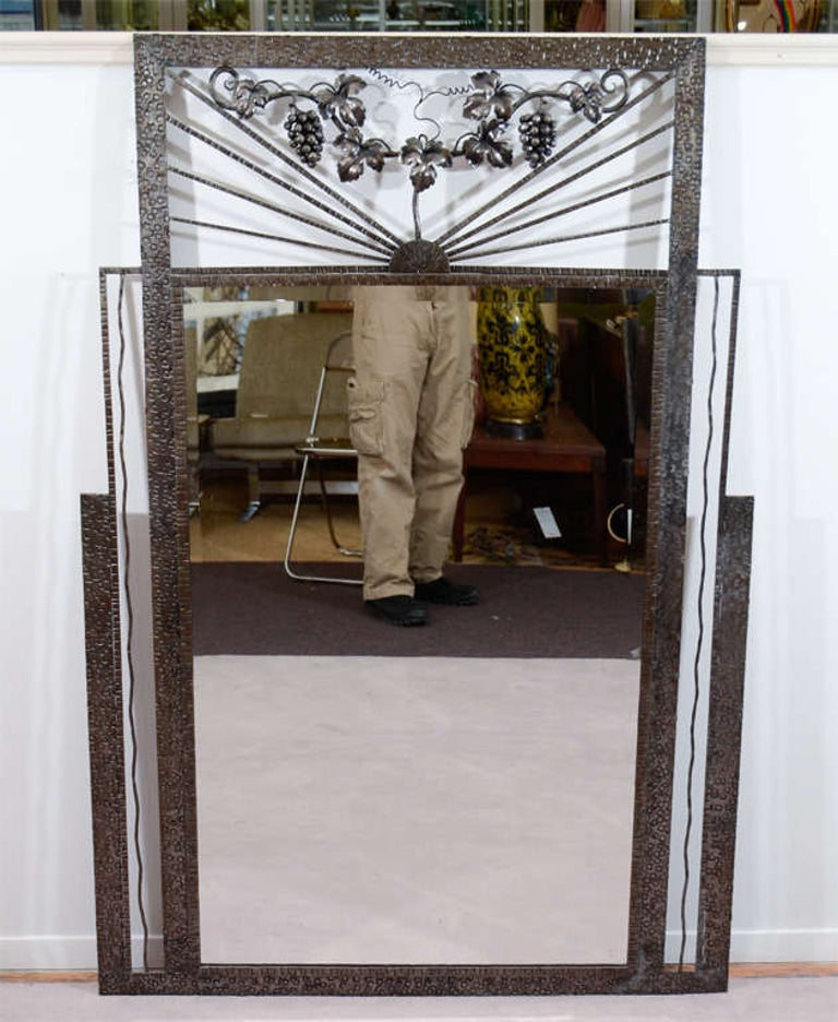 An original Art Deco mirror surrounded by a worked iron frame. The frame above the mirror is decorated with a grape vine with grapes and leaves. Good condition with age appropriate patina and wear; there is some spotting on the upper left side of