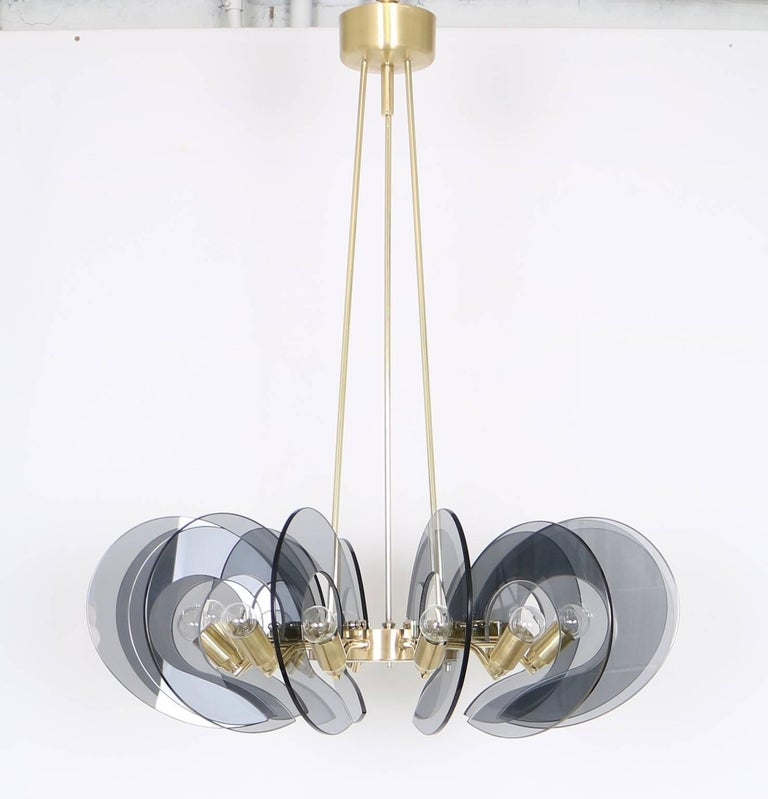 12-light chandelier, attributed to Fontana Arte, manufactured in Italy circa 1950s, brass ring frame with brushed and polished finishes, holding in suspension blue-tinted glass semi-circle panels. Completely restored and adapted to US standard,