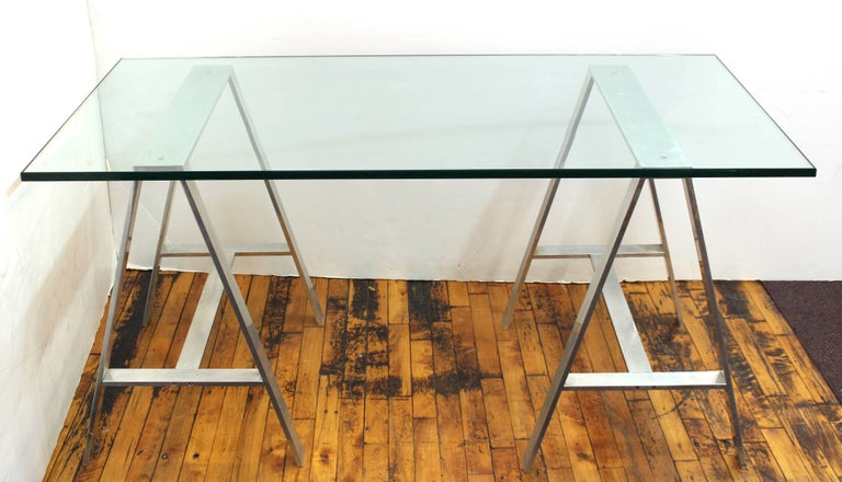 A Mid-Century Modern saw horse desk with an aluminium base and a thick 3/4 inch glass top. The piece was made in the United States in the 1970s and is in very good vintage condition.