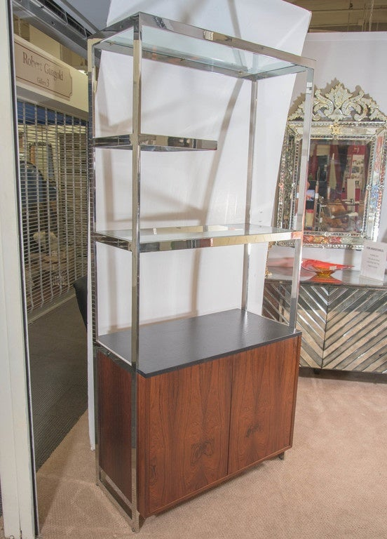 A vintage, modernistic cabinet, veneered in walnut, with attached etagere in chrome, inset with glass top shelves, produced circa 1960s by designer Milo Baughman. Very good vintage condition, with some age appropriate wear.