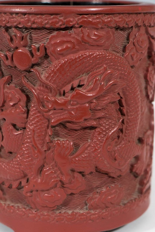 A Chinese cinnabar pot, produced within the Daoguang period (1821-1850), the body beautifully carved, detailing two celestial dragons, the interior painted in black lacquer. Markings include signature on the bottom of the piece. Very good antique