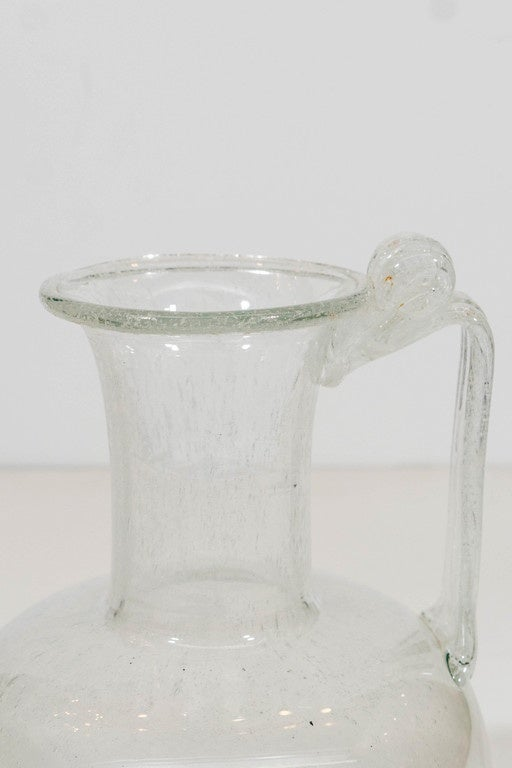 A vintage Venetian glass ewer or pitcher, features clear glass body with infused bubbles, and a handle that is finished with a decorative fold-over at the funnel mouth. Good vintage condition, with crackalure over the neck and handle.