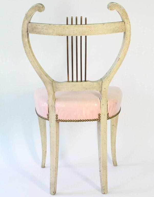 A set of four French vintage dining chairs, designed in the Regency style and produced circa 1950-1960, each with painted wood frames on Klismos legs and pink vinyl seats, lined with brass nailhead studs, the stylistic lyre backs accented with brass