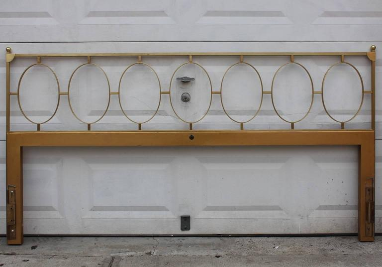 A vintage king size brass headboard, produced circa 1970s, and detailed with modern geometric oval rings, set against a highly linear frame. Overall good condition, with minimal wear and patina, consistent with age.  9494