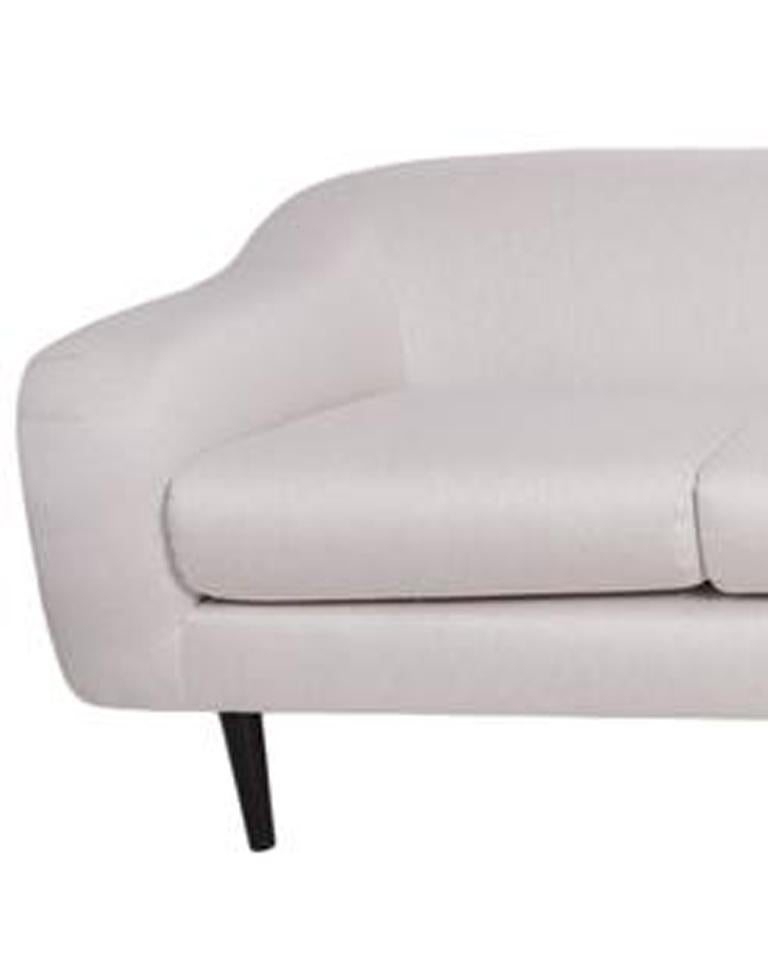 A lengthy four-seat sofa by Joaquim Tenreiro, produced circa 1950s, upholstered in off-white linen, with curved arms, raised on tapered legs in Brazilian jacaranda. Very good vintage condition, recently re-upholstered.  10841