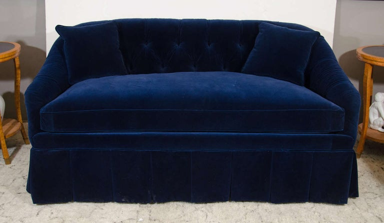 A button tufted velvet settee in midnight blue. Good condition, wear consistent with age and use.