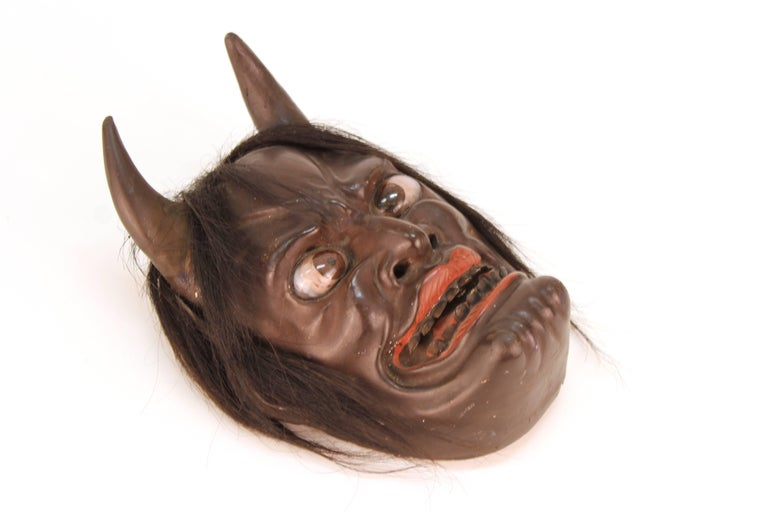 A Japanese sculpted wood Ike mask produced during the Edo Period (1603-1868) around 1850, depicting a devil face. Highly detailed, the mask has inserted eyes and hair attached to it.