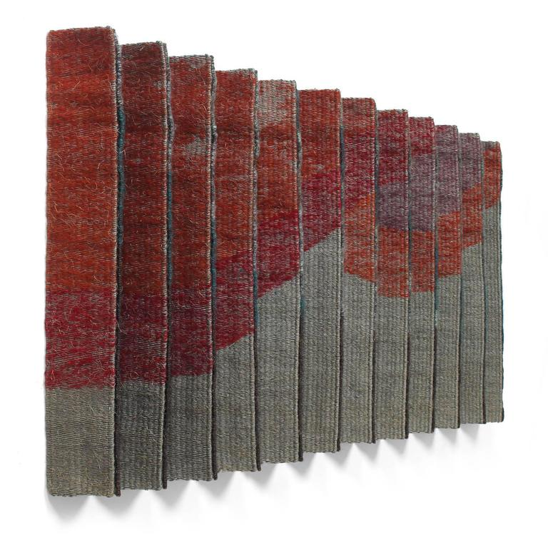 A unique wall hanging fashioned of conjoined and pleated hand woven wool panels in abstracted patterns in tones of black, gray and red.