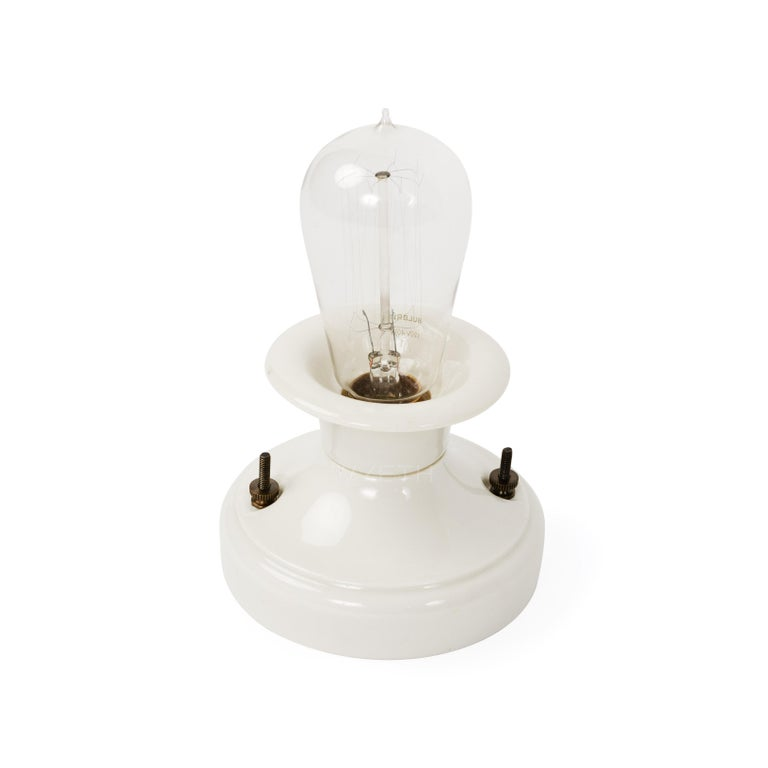 A white porcelain bowl-form wall sconce or ceiling lamp.