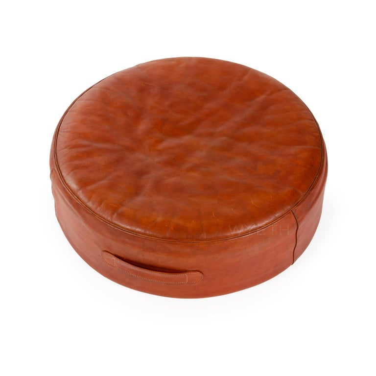 A round leather ottoman / stool retaining the original red leather upholstery and leather handle.