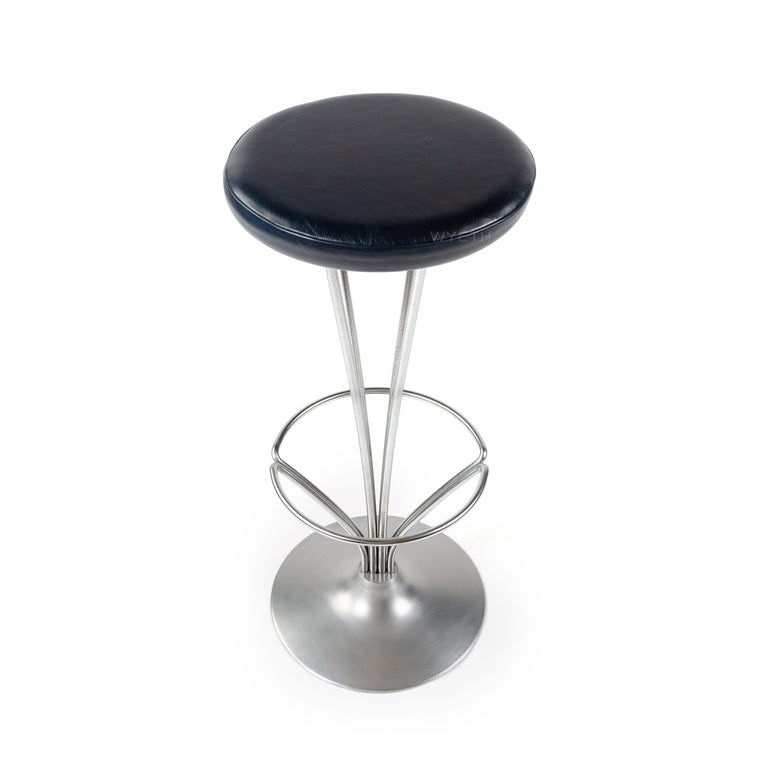 A unique pedestal style barstool with satin chromed steel bars that slightly arch to support a foot rest and upholstered seat in dark blue leather.